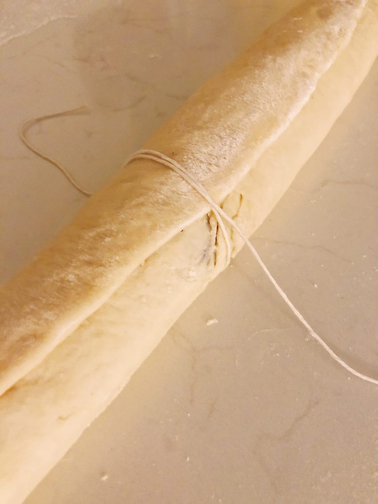 You kitchen twine to cut your dough. Start in the middle and cut in half, then cut the 1/2's in half and so on.